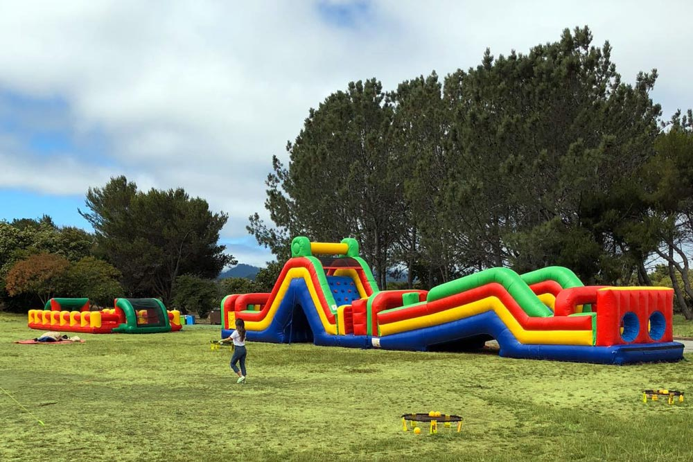 interactive inflatable bouncy combos and party game rentals set up in field